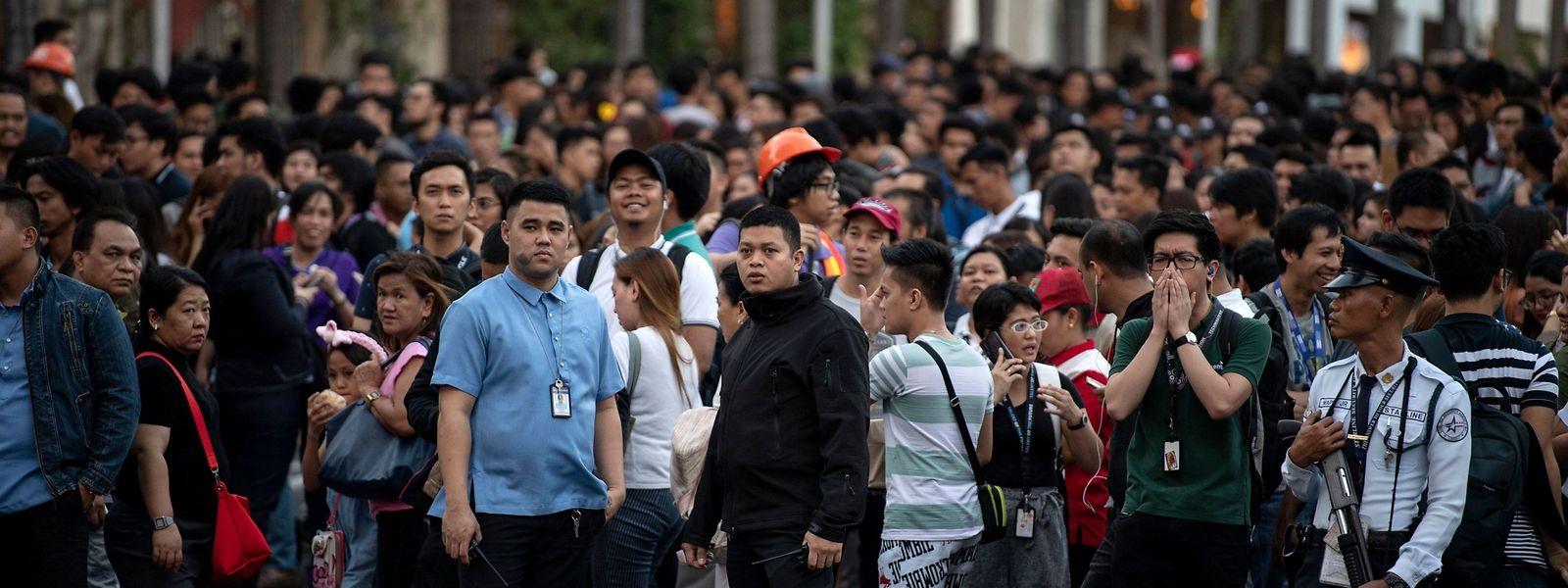 Menschen versammeln sich unter freiem Himmel in den Straßen von Manila, nach einem Erdbeben im Norden des Landes.