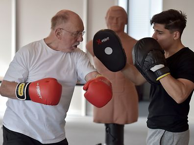 A cancer patient takes part in a boxing training session with coach Thibault Kuhn (R) in a hospital of Strasbourg, eastern France, on October 6, 2016. Seven cancer patients, from 40 to 80 years old attend a unique boxing activity at the Paul-Strauss cancer treatment centre to work on their balance, coordination, sequence memorising and muscles strengthening. / AFP PHOTO / PATRICK HERTZOG