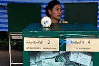 Bangkok: Eine Wahlhelferin sitzt in einem Wahllokal hinter einer Urne.