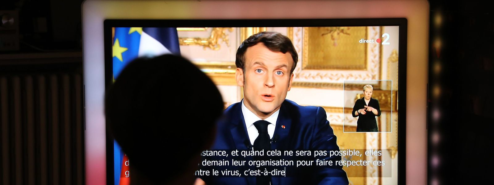 French President Emmanuel Macron is seen on a television screen as he speaks during a televised address to the nation on the outbreak of COVID-19, caused by the novel coronavirus, on March 16, 2020, in Paris. - The French president addresses the nation, with many expecting him to unveil more strict home confinement rules in a bid to prevent the virus from spreading. France has closed down all schools, theatres, cinemas and a range of shops, with only those selling food and other essential items allowed to remain open. The balance sheet of the epidemic climbed to 127 dead and 5,423 confirmed cases in France. (Photo by Ludovic Marin / AFP)