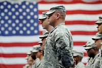 ARCHIV - 10.12.2008, Hessen, Wiesbaden: US-Soldaten stehen nach ihrer Ankunft auf der US-Airbase in Wiesbaden-Erbenheim vor einer US-Flagge. Die US-Regierung wird an diesem Mittwoch voraussichtlich Einzelheiten zum geplanten Abzug eines Teils der amerikanischen Truppen aus Deutschland bekanntgeben. (zu dpa «Einzelheiten zu US-Teilabzug aus Deutschland erwartet» vom 29.07.2020) Foto: Frank May/dpa +++ dpa-Bildfunk +++