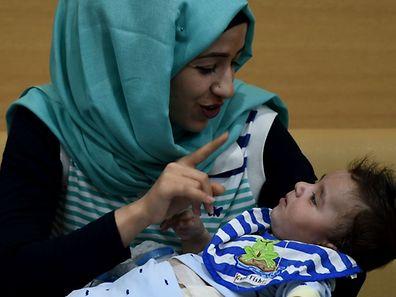 La maman de Karam le tenant dans ses bras, après l'opération