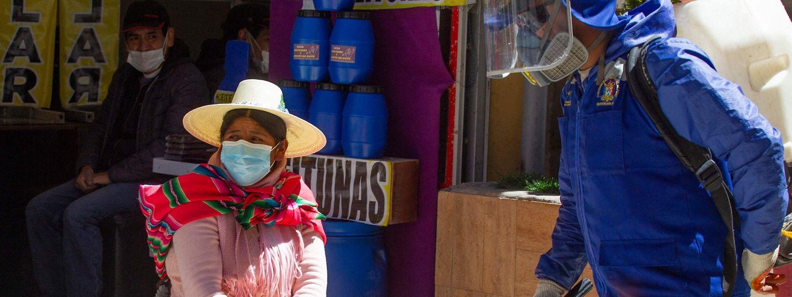 Im peruanischen Puno sprüht ein Arbeiter Desinfektionsmittel auf die Straße.