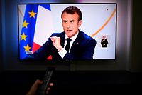 "A person looks at a television screen showing French President Emmanuel Macron during his live address following the ""Great National Debate"" at the Elysee Palace in Paris on April 25, 2019, in Rennes,  western France. - President Emmanuel Macron on April 25, 2019 vowed to press ahead with his government's programme to transform France, adding public order must be restored after months of protests. (Photo by Damien MEYER / AFP)"