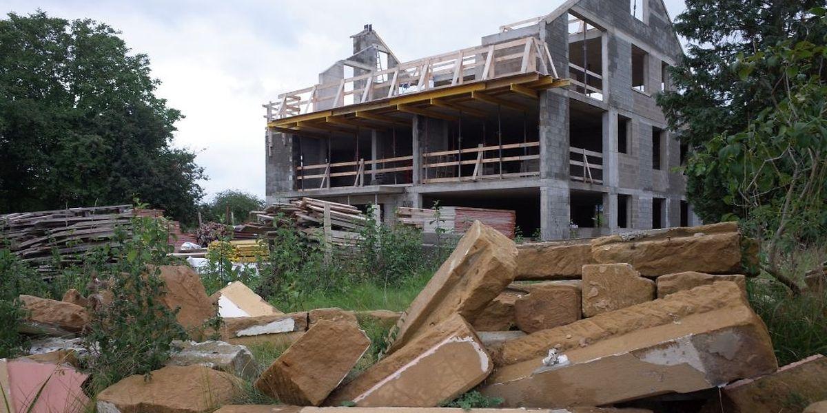 Während im Hintergrund ein Neubau entsteht, zeugen auf dieser Baustelle in der Rue des Potiers in Nospelt, nur mehr die Sandsteine vom Haus, das einst hier stand.