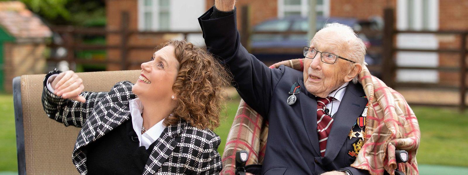 """Captain Tom und seine Tochter Hannah schauen den """"Battle of Britain Memorial""""-Flugzeugen zu, die zu seinen Ehren am Himmel vorbeiziehen."""