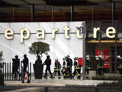 French firefighters and RAID police unit officers secure Paris' Orly airport on March 18, 2017 following the shooting of a man by French security forces.