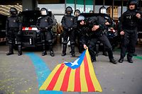A member of the Catalan regional police force Mossos d'Esquadra picks up a Catalan pro-independence Estelada flag to return it to the protester who placed it in front of the police during a demonstration calling for the release of Catalonia's former president outside the Barcelona-Sants train station in Barcelona on March 27, 2018, two days after he was arrested in Germany. Spanish riot police broke up a blockade by Catalan separatists on major motorways in Catalonia Tuesday, part of a wave of protests over the arrest and detention of ex-regional president Carles Puigdemont. / AFP PHOTO / Josep LAGO