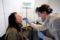 A medical staff member takes a sample from the mouth of a student at a newly-opened coronavirus testing centre for students at the KULeuven University, in Leuven, on October 19, 2020, as part of the special safety and security measures taken to prevent the spread of COVID-19 (novel coronavirus). (Photo by ERIC LALMAND / BELGA / AFP) / Belgium OUT