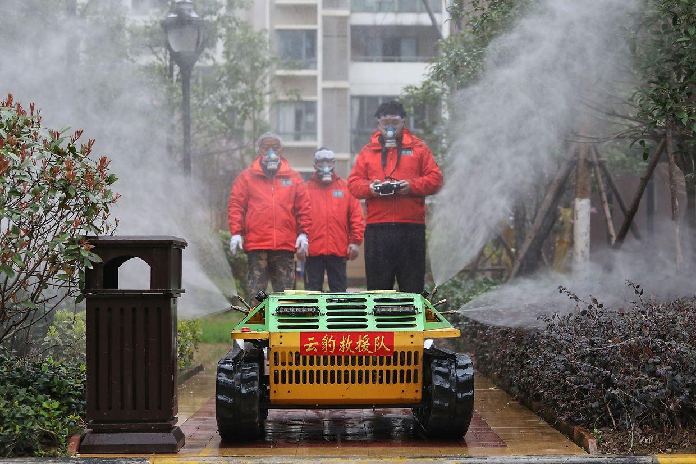 Im chinesischen Wuhan versprühen Freiwillige Desinfektionsmittel mit einem Roboter.