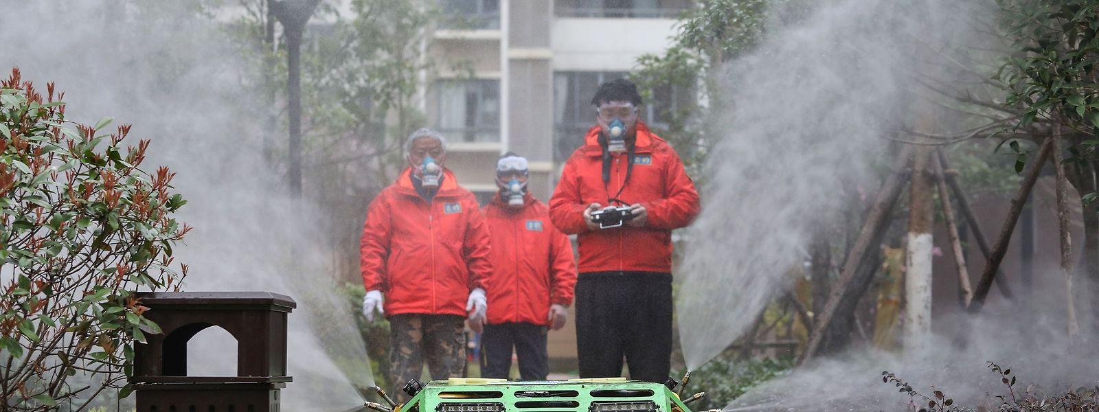Freiwillige versprühen im chinesischen Wuhan Desinfektionsmittel mit einem ferngesteuerten Roboter.
