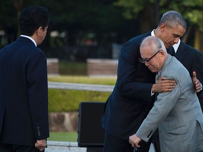 TOPSHOT - Japanese Prime Minister Shinzo Abe (L) looks on as US President Barack Obama (2nd R) hugs a survivor of the 1945 atomic bombing of Hiroshima, during a visit to the Hiroshima Peace Memorial Park on May 27, 2016. Obama on May 27 paid moving tribute to victims of the world's first nuclear attack.   / AFP PHOTO / JIM WATSON