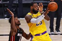LAKE BUENA VISTA, FLORIDA - OCTOBER 06: LeBron James #23 of the Los Angeles Lakers passes the ball as Jimmy Butler #22 of the Miami Heat defends during the fourth quarter in Game Four of the 2020 NBA Finals at AdventHealth Arena at the ESPN Wide World Of Sports Complex on October 6, 2020 in Lake Buena Vista, Florida. NOTE TO USER: User expressly acknowledges and agrees that, by downloading and or using this photograph, User is consenting to the terms and conditions of the Getty Images License Agreement.   Kevin C. Cox/Getty Images/AFP == FOR NEWSPAPERS, INTERNET, TELCOS & TELEVISION USE ONLY ==