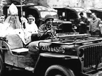 Richard Brookins is seen dressed as St Nick being ferried around Wiltz in a Jeep on December 5, 1944
