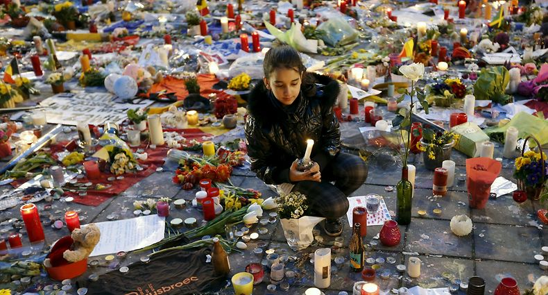 A girl lights a candle as people pay tribute to the victims of Tuesday's bomb attacks at the Place de la Bourse in Brussels, Belgium, March 26, 2016.  REUTERS/Francois Lenoir