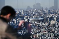 (FILES) In this file photo taken on March 25, 2020, people look out from a highrise viewing area at the newly-built Japan National Stadium, the main venue for the 2020 Olympic Games, in Tokyo, the day after the historic decision to postpone the 2020 Tokyo Olympic Games. - The shock postponement of the Tokyo 2020 Olympics has dealt a savage blow to Japan's hotels and tourism industry already reeling from the impact of the coronavirus pandemic. (Photo by CHARLY TRIBALLEAU / AFP) / To go with AFP story Japan-Oly-Tokyo-economy-tourism-hotels, FOCUS by Kyoko HASEGAWA