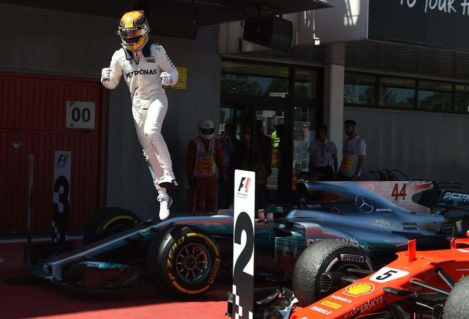 Mercedes' British driver Lewis Hamilton jumps from his car as he celebrates winning at the Circuit de Catalunya on May 14, 2017