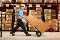 A warehouse worker wearing a protective mask and a hard hat pushes a hand truck and a stack of boxes in a warehouse stacked with inventory.