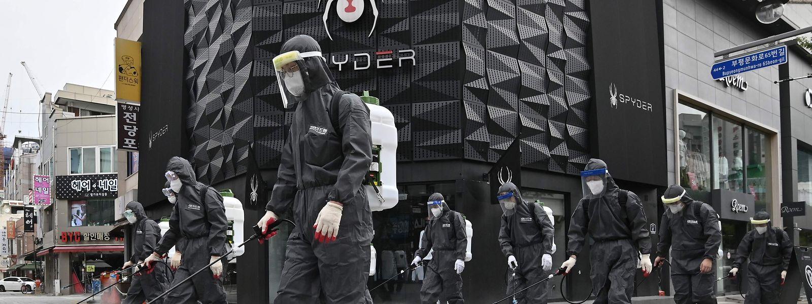 Gesundheitsbeamte in Schutzkleidung versprühen Desinfektionsmittel in der südkoreanischen Stadt Incheon.