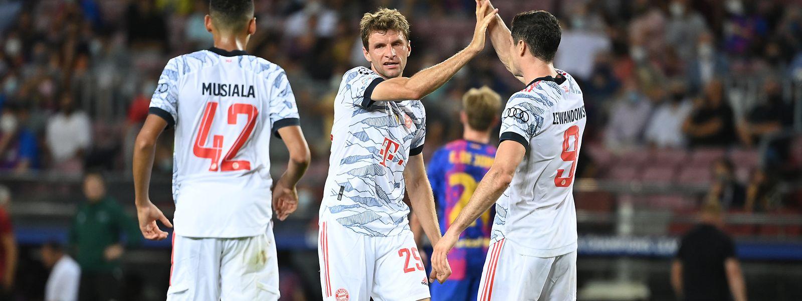 Münchens Mittelfeldspieler Jamal Musiala (l-r), Münchens Mittelfeldspieler Thomas Müller und Münchens Stürmer Robert Lewandowski freuen sich über das Tor von Müller zum 0:1.