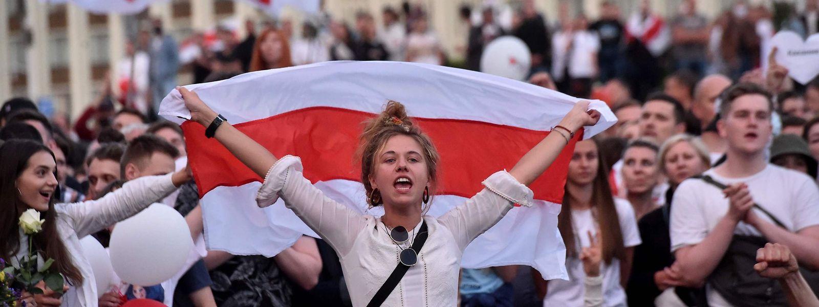 Minsk: eine Frau hält eine weisrussische Flagge bei einer Demonstraktion gegen Machthaber Lukaschenko.