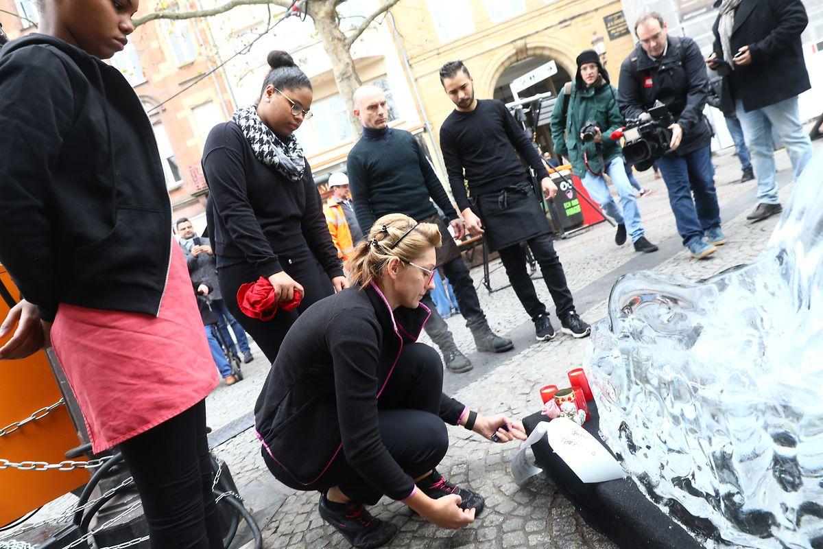 Am Montagmorgen legten Menschen am Unglücksort Blumen um einen Schlitten aus Eis nieder.