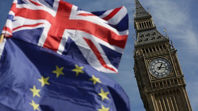 """(FILES) This file photo taken on March 25, 2017 shows an EU flag and a Union flag held by a demonstrator is seen with Elizabeth Tower (Big Ben) and the Houses of Parliament as marchers taking part in an anti-Brexit, pro-European Union (EU) march enter Parliament Square in central London on March 25, 2017, ahead of the British government's planned triggering of Article 50 next week. EU migrants said on June 23 that far from being """"generous"""", Prime Minister Theresa May's offer for their post-Brexit residency was niggardly and left them prey to the whims of British lawmakers. One year ago today on June 23, 2016 Britain voted to leave the European Union. / AFP PHOTO / DANIEL LEAL-OLIVAS"""