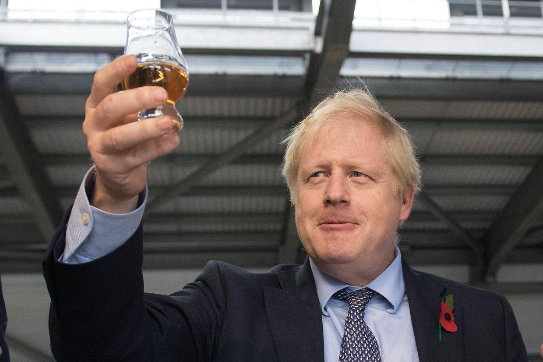 Boris Johnson, Premierminister von Großbritannien, hält ein Glas Whisky während seines Besuchs der Whiskybrennerei Roseisle in Schottland.