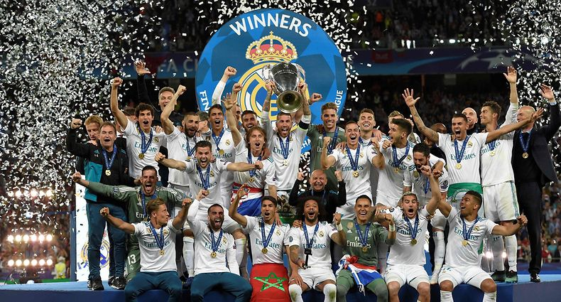 Real Madrid's Spanish defender Sergio Ramos (C) holds the trophy after winning the UEFA Champions League final football match between Liverpool and Real Madrid at the Olympic Stadium in Kiev, Ukraine on May 26, 2018. Real Madrid defeated Liverpool 3-1. / AFP PHOTO / LLUIS GENE