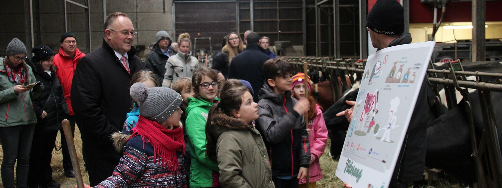 Joé Biver vom Milchproduzenten Biver-Haan (r.) erklärt den Schülern des Zyklus 3.1 aus Kehlen in Präsenz von Landwirtschaftsminister Romain Schneider, wie die Milch produziert wird.