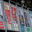 FILE PHOTO: A man looks at campaign posters of the 11th candidates who run in the 2017 French presidential election in Enghien-les-Bains, near Paris, France April 19, 2017. REUTERS/Christian Hartmann/File Photo