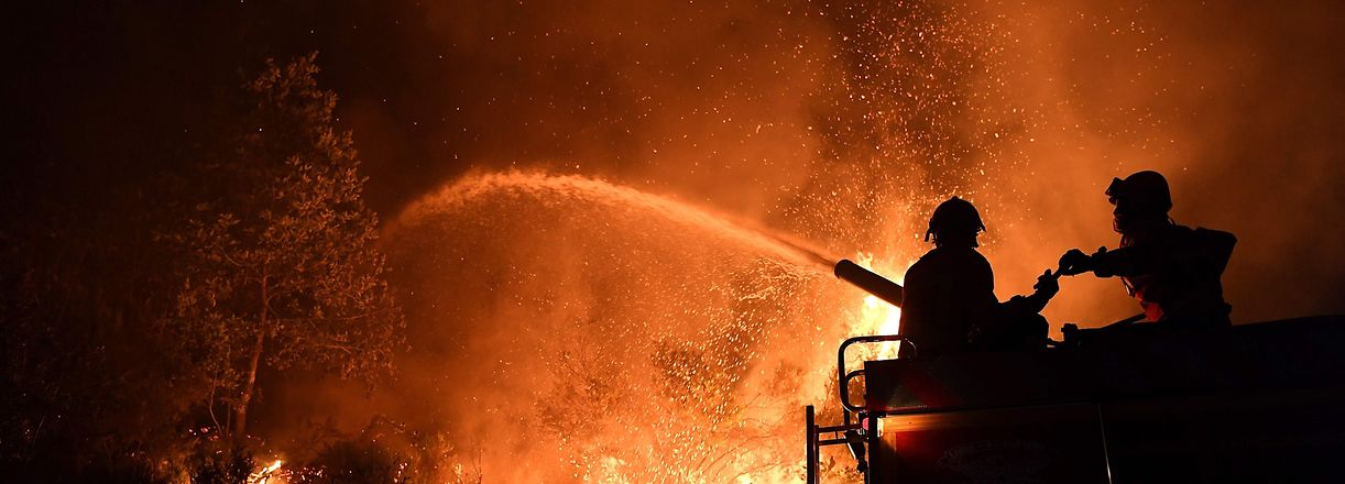 Firefighters try to extinguish a wildfire in Colmeal, near Gois on the night of June 21, 2017.  The huge forest fire that erupted on June 17, 2017 in central Portugal killed at least 64 people and injured 135 more, with many trapped in their cars by the flames. / AFP PHOTO / FRANCISCO LEONG