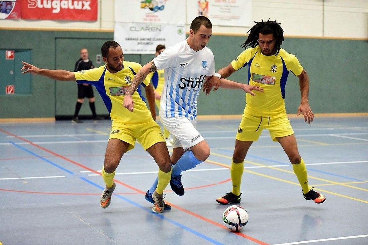Le joueur du FC Nordstad Steve Ackels (en blanc et bleu) est coincé dans l'étau formé par Nelito dos Santos da Cruz (à dr,) et Nadir Almeida Martins, du FC Bettendorf.