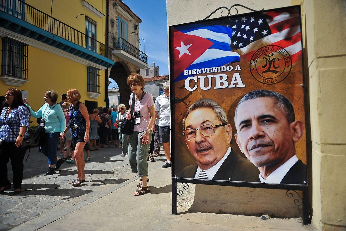 Touristen flanieren an einem Poster mit den Porträts der beiden Präsidenten Castro und Obama vorbei.