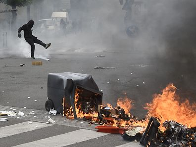 A trash can burns in the street as protesters clash with anti-riot police during a rally against the French government's labour law reforms in Rennes, western France, on April 28, 2016. Protesters clashed with police in Paris and western France on April 28 as workers and students across the country made a new push for the withdrawal of a hotly contested labour bill. Demonstrations as well as work stoppages, notably in the aviation and public transport sectors, are planned across France in the latest actions in a protest wave that began two months ago.  / AFP PHOTO / DAMIEN MEYER