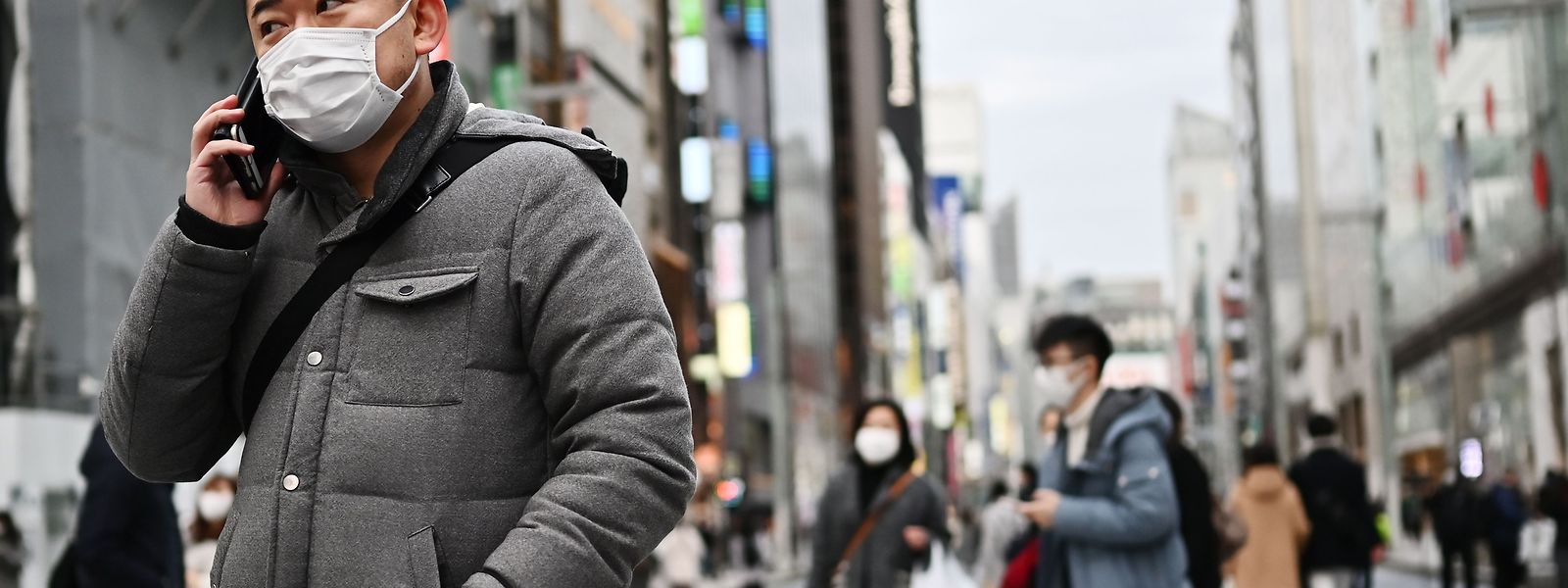 Pedestrians wearing protective masks to help stop the spread of a deadly virus which began in the Chinese city of Wuhan, walk on a street in Tokyo's Ginza area on January 25, 2020. - Japan's health authorities on January 25 confirmed the country's third case of the coronavirus which emerged in the Chinese city of Wuhan. (Photo by CHARLY TRIBALLEAU / AFP)