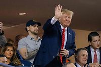 US President Donald Trump (C) waves as US First Lady Melania Trump looks on as they watch Game 5 of the World Series between the Washington Nationals and Houston Astros at Nationals Park in Washington, DC on October 27, 2019. (Photo by TASOS KATOPODIS / AFP)