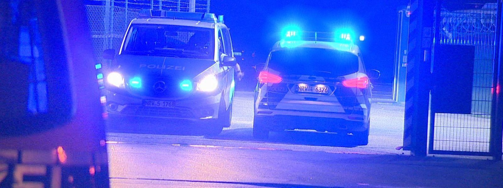 Polizisten passieren in Polizeifahrzeugen ein Tor am Flughafen Weeze.