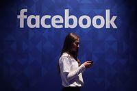 ARCHIV - 03.11.2015, Großbritannien, London: Eine Frau steht mit ihrem Smartphone unter dem Facebook-Schriftzug. Facebook prescht im Geschäft mit VR-Brillen mit einer deutlichen Preissenkung vor. Das neue Modell der Brille Oculus Quest, die ohne einen zusätzlichen Computer auskommt, wird in den USA 299 Dollar kosten - 100 Dollar weniger als die Vorgängerversion, wie Facebook am Mittwoch ankündigte. Foto: Niall Carson/PA Wire/dpa +++ dpa-Bildfunk +++
