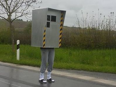 The groom-to-be dressed as a speed camera, posing for a photo on a road near Stadbredimus.