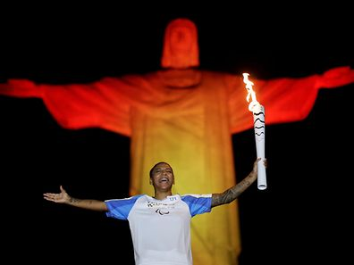2016 Rio Paralympics - Olympic torch - Rio de Janeiro, Brazil - 06/09/2016. Brazil's judo athlete Rafaela Silva holds the Olympic torch during a ceremony with the Paralympic torch at the Christ the Redeemer statue ahead of the 2016 Rio Paralympic games. REUTERS/Ueslei Marcelino     TPX IMAGES OF THE DAY