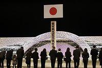 Angehörige der Opfer der Erdbebenkatastrophe von Fukushima legen während der Gedenkfeier Blumen nieder.