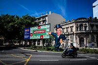 A man rides a motorbike next to an Iniciativa Liberal party electoral campaign billboard depicting a caricatured Portuguese Prime Minister Antonio Costa in Lisbon on October 1, 2019, ahead of October 6 general election. (Photo by PATRICIA DE MELO MOREIRA / AFP)