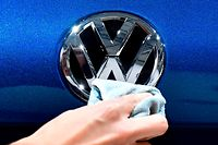 A staff member cleans a logo of an SUV VW Touareg on display ahead of the annual general meeting of German carmaker Volkswagen, in Berlin on May 3, 2018. / AFP PHOTO / Tobias SCHWARZ