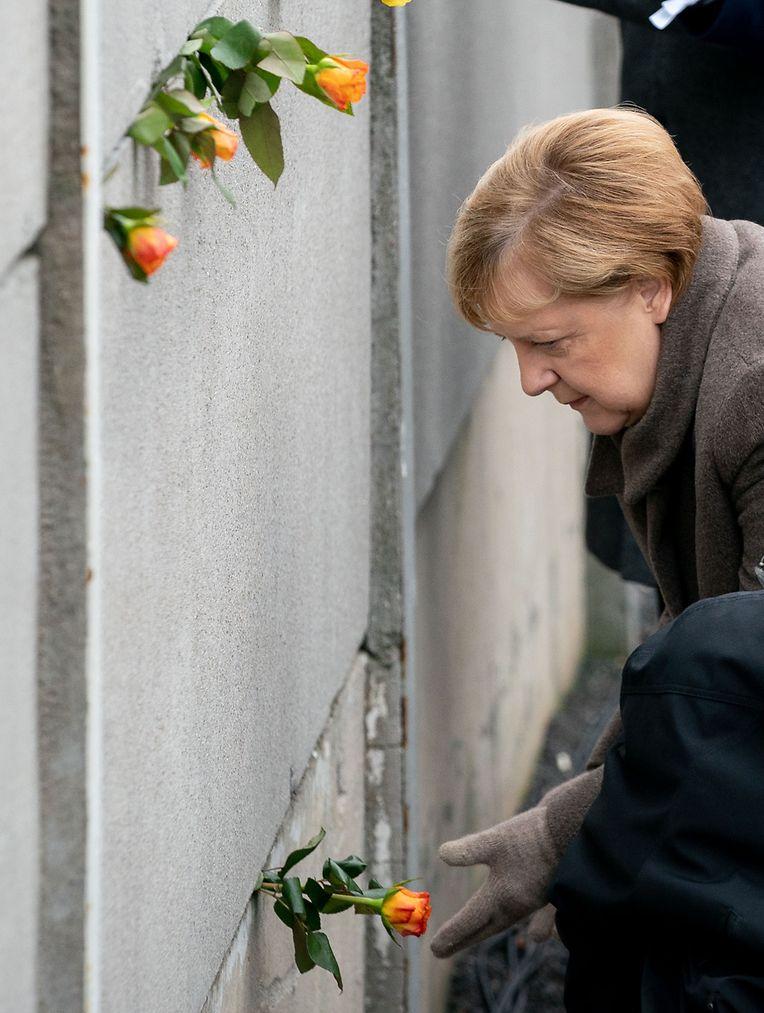 Berlin: Besucher stecken Blumen bei der Gedenkveranstaltung der Stiftung Berliner Mauer an der Bernauer Straße in Mauerschlitze der Hinterlandmauer.