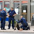 TOPSHOT - Police officers stand next to a person lying on the pavement in the Finnish city of Turku where several people were stabbed on August 18, 2017. Several people were stabbed in the southwestern Finnish city of Turku, police said after shooting and arresting a suspect. Public television station Yle reported that central Turku was on lockdown, with witnesses saying they had seen bodies lying on the ground in a busy area of the town. Businesses were shut. / AFP PHOTO / Kirsi Kanerva
