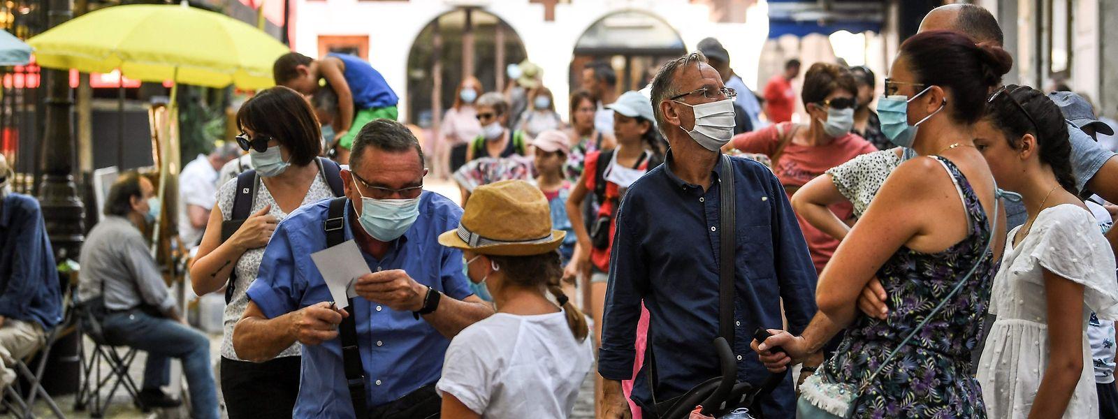 Maskierte Besucher besichtigen Montmartre in Paris.