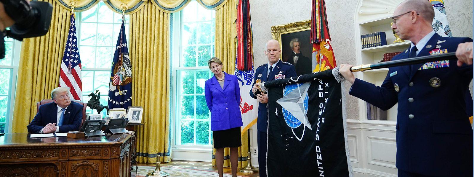 """Trump sieht sich die """"Space Force""""-Flagge im Oval Office an."""