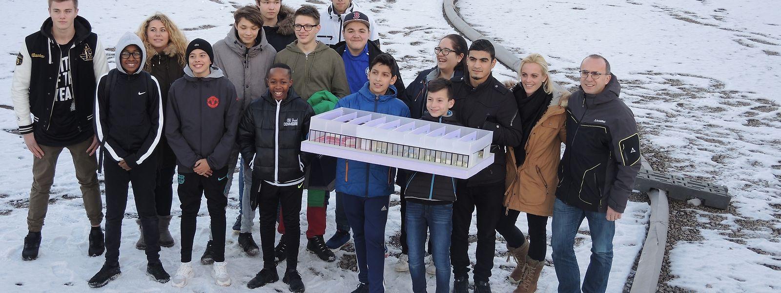 """Ein Teil der Jugendlichen samt Betreuer und Verantwortlichen des """"Jugendtreff Déifferdeng"""" mit dem Endentwurf auf der Baustelle."""