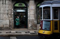 A tram passes by a shopkeeper wearing a face mask in downtown Lisbon on November 7, 2020. - The Portuguese government is holding an extraordinary ministers' council to decide on concrete measures to fight the spread of the coronavirus, which could include a night curfew as it already exists in several European countries. (Photo by PATRICIA DE MELO MOREIRA / AFP)